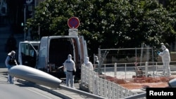 French police conduct an investigation in the French port city of Marseille after one person was killed and another injured after a vehicle crashed into two bus shelters, August 21, 2017.