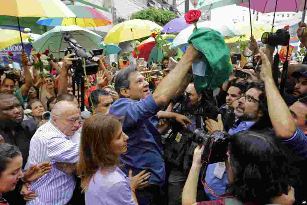Workers' Party presidential candidate Fernando Haddad holds a Brazilian flag after casting his vote in the presidential election in Sao Paulo, Brazil.
