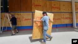 Warga melindungi kaca-kaca jendela rumahnya dengan kayu lapis sebagai persiapan menjelang datangnya topan Harvey di Corpus Christi, Texas (24/7).