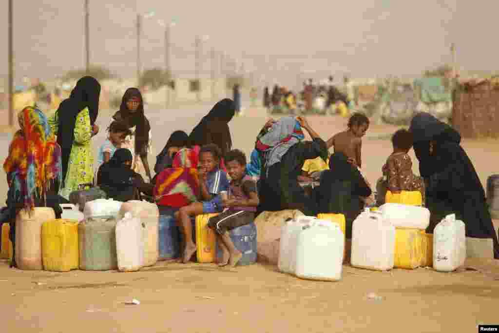 Phụ nữ và trẻ em đi hứng nước trong một trại dành cho những người phải dời cư trong nước. Trại nằm trong tỉnh Hajja của Yemen.