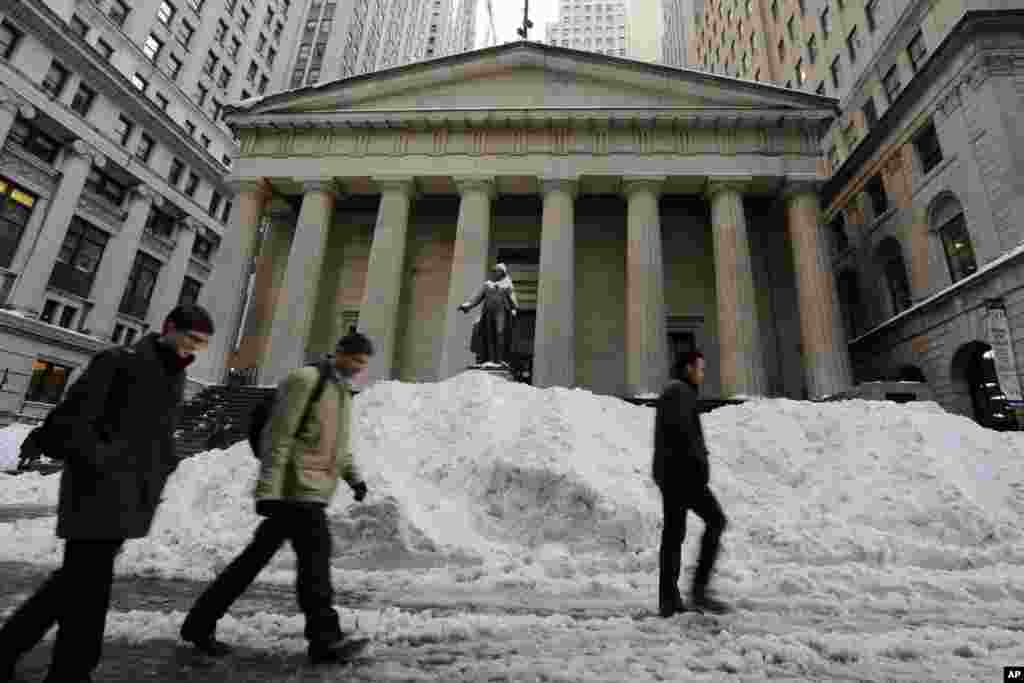 Morning commuters pass snow on Wall Street in front of Federal Hall in New York's Financial District, Jan. 25, 2016.