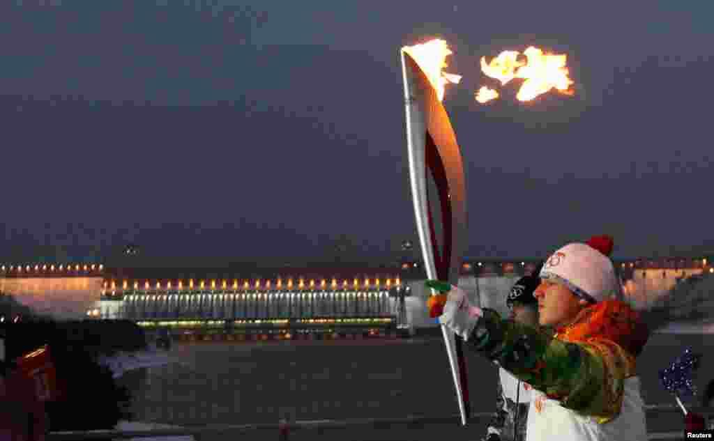 A runner carries the Sochi 2014 Winter Olympic torch along a bridge across Yenisei River near the Krasnoyarsk hydro electric power station near the town of Divnogorsk outside Krasnoyarsk, Russia.