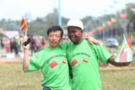 An unidentfied Chinese national and a Zimbabwean man hug while welcoming Chinese President Xi Jinping upon his arrival in Harare, Zimbabwe, Tuesday, Dec. 1. 2015.