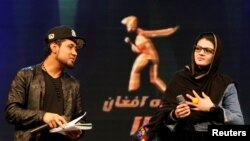 """FILE - Zulala Hashimi, 18, right, and Sayed Jamal Mubarez, 23, finalists of the music contest """"Afghan Star,"""" rehearse for the show in Kabul, Afghanistan, March 19, 2017."""