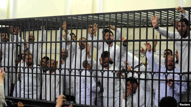 Supporters of former Egyptian president File - Mohamed Morsi, standing trial on charges of violence that broke out in Alexandria last year, react after two fellow supporters were sentenced to death, in a court in Alexandria, March 29, 2014.
