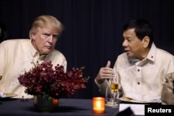 U.S. President Donald Trump talks with Philippines President Rodrigo Duterte during the gala dinner marking ASEAN's 50th anniversary in Manila, Philippines, Nov. 12, 2017.