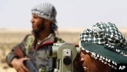 一名利比亚反政府力量战士在用仪器观察地形