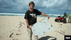 FILE - An undated handout photograph made available June 10, 2016, by Blaine Alain Gibson shows Gibson holding pieces of debris possibly belonging to the missing Malaysian Airlines plane MH370, which were found on Nosy Boraha island, Madagascar.