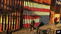 FILE - People pass graffiti along a border structure in Tijuana, Mexico, Jan. 25, 2017. Despite harsher policies instituted by the Trump administration, the U.S. still has lure for Mexicans seeking a better life.