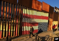 "FILE - People pass graffiti along an existing border structure in Tijuana, Mexico, Jan. 25, 2017. One U.S. lawmaker, opposed to the wall, quipped ""We need a modern, functioning, immigration system. Not a wall."""