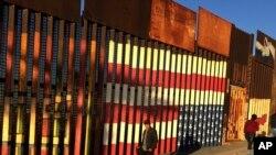 People pass graffiti along the border structure in Tijuana, Mexico, Jan. 25, 2017.