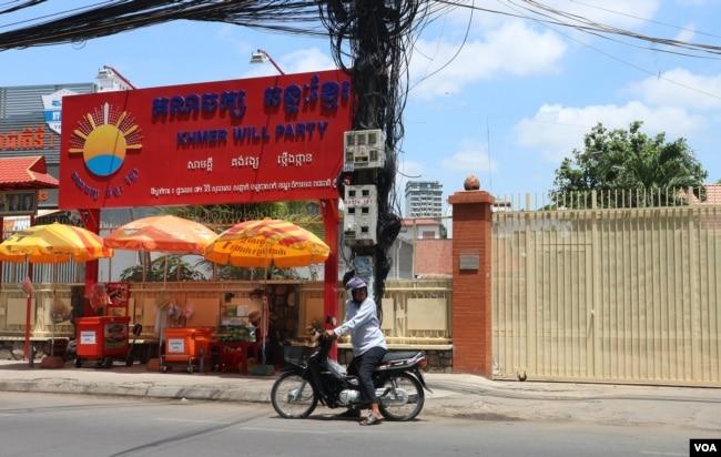 បុរសម្នាក់ឈប់ម៉ូតូនៅខាងមុខទីស្នាក់ការគណបក្សឆន្ទៈខ្មែរក្នុងខណ្ឌចំការមន ដែលកំពុងបិទទ្វារ នាថ្ងៃបើកយុទ្ធនាការថ្ងៃទី១នៃការឃោសនារកសំឡេងគាំទ្រសម្រាប់ការបោះឆ្នោតជ្រើសរើសក្រុមប្រឹក្សា អាណត្តិទី៣ នៅថ្ងៃទី១៧ ខែឧសភា ឆ្នាំ២០១៩។ (កាន់ វិច្ឆិកា/VOA Khmer)