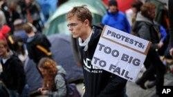 """一名英国青年10月16日在伦敦金融城的圣保罗大教堂外手举标语牌参加全球""""占领""""运动"""