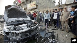 People inspect a destroyed car and a wheelchair at the scene of a car bomb attack that ripped through a funeral tent in a mainly Shiite area in Baghdad, Iraq, January 27, 2011