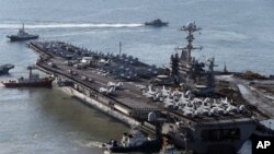 USS George Washington is escorted into a navy port in Busan, South Korea, Oct. 4, 2013.
