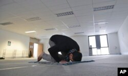 FILE - In this July 13, 2015, photo, Minhaj Uddin Syed prays at a temporary musalla (prayer room) set up for the holy month of Ramadan in the central business district of Sydney, Australia.