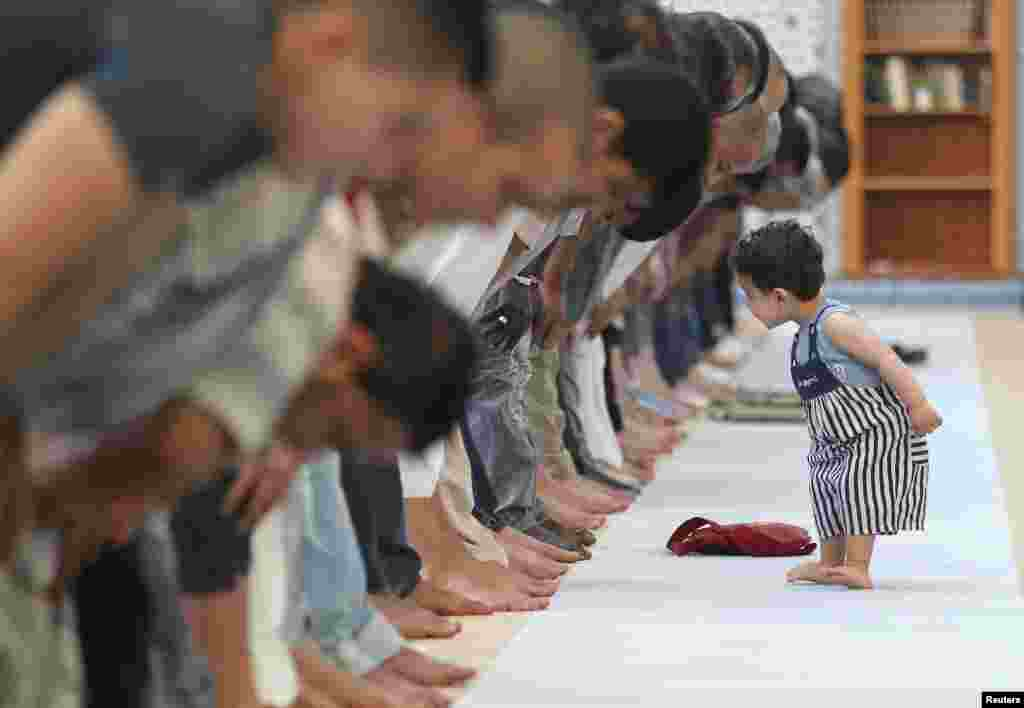 A child walks near members of the Muslim community attending midday prayers at Strasbourg Grand Mosque in Strasbourg, France, on the first day of Ramadan.