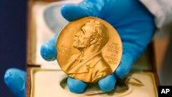 Seorang pegawai perpustakaan nasional memperlihatkan medali emas Nobel yang diberikan kepada mendiang novelis Gabriel Garcia Marquez, di Bogota, Kolombia, 17 April 2015. (Foto: dok).