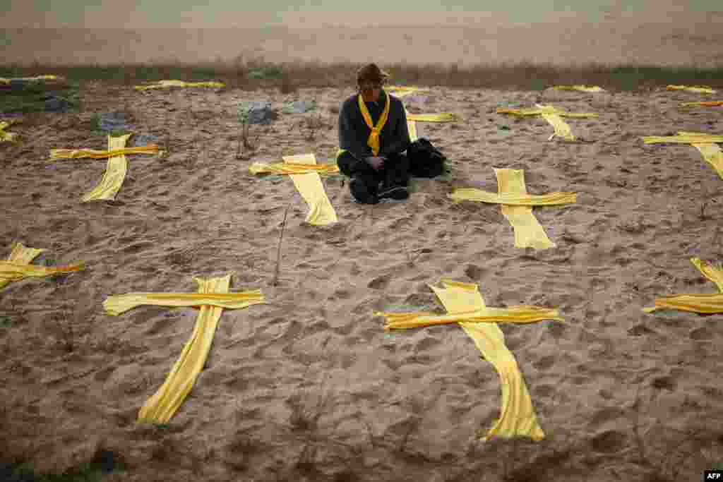 A woman sits on the beach among yellow crosses during a protest called by local Republic Defence Committees (CDR), in support for jailed separatist leaders, at Mataro's beach, near Barcelona, Spain.