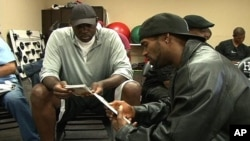 Basketball coaches in Los Angeles study program materials prepared by the San Francisco-based Family Violence Prevention Fund, during a Coaching Boys into Men session