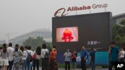 FILE - Visitors walk past a giant display at the Alibaba Group headquarters in Hangzhou, in eastern China's Zhejiang province, May 27, 2016.