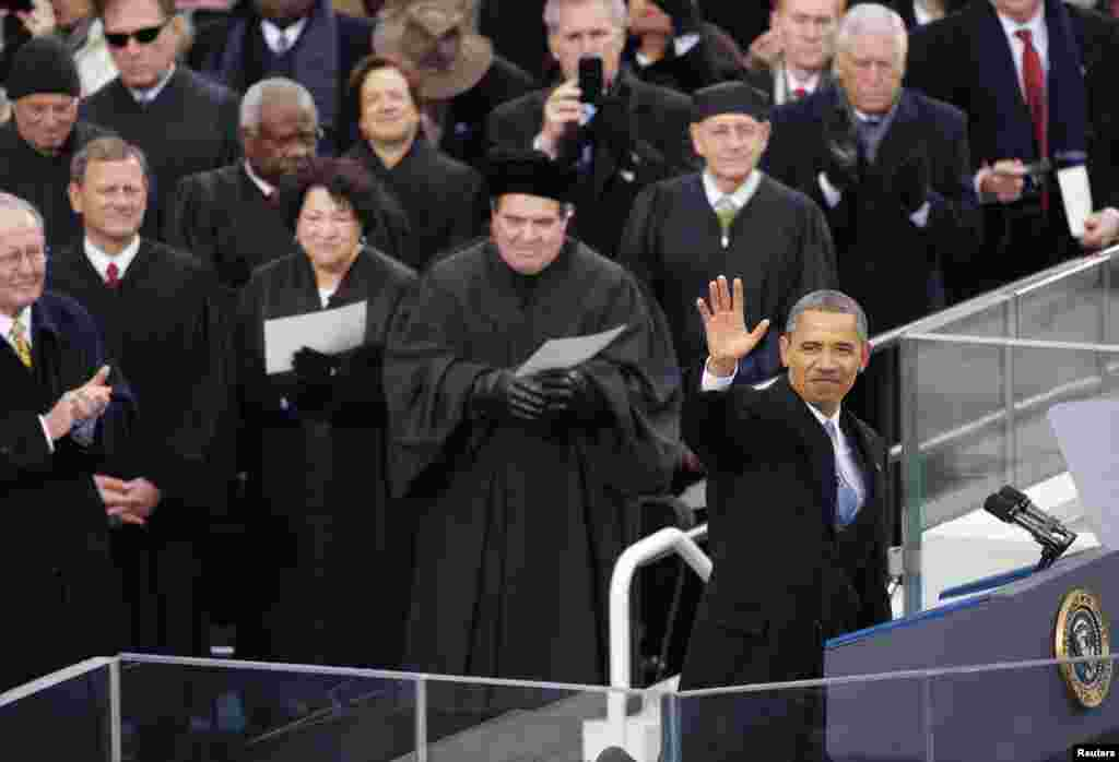 U.S. President Barack Obama waves during ceremonial swearing-in ceremonies on the West front of the U.S Capitol in Washington, January 21, 2013