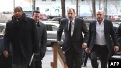 Харви Вайнштейн (второй справа) заходит в здание суда в Нью-Йорке