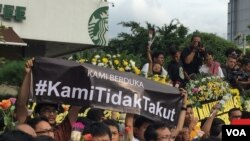 """A banner reading """"We Are Not Afraid"""" is held aloft during a vigil at the site of the Jakarta terrorist attack, Jakarta, Indonesia, Jan. 15, 2016. (S. Herman/VOA News)"""