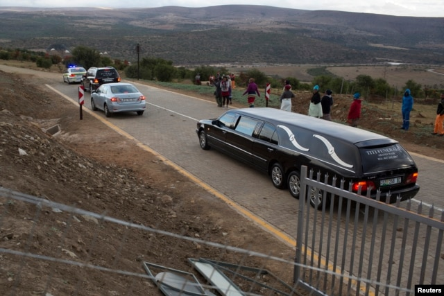 A convoy of police and funeral vehicles approaches the home of Mandla Mandela, a grandson of ailing former S. African President Nelson Mandela, following a court hearing clearing the way to remove the remains of the former leader's children from his prope