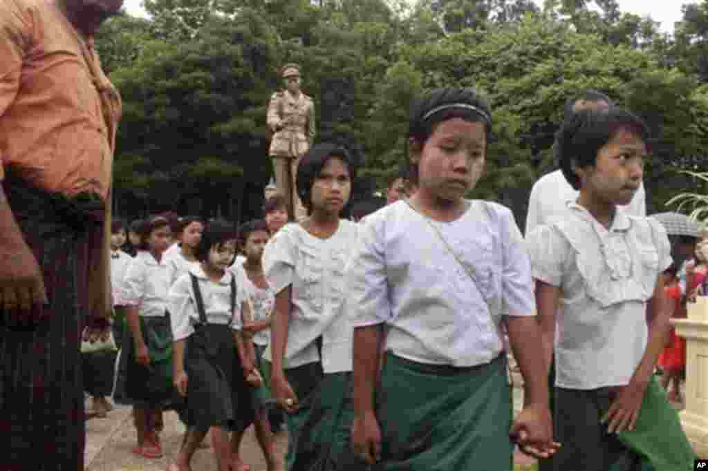 School children leave after paying a visit to the statue of Gen. Aung San, the late father of Myanmar opposition leader Aung San Suu Kyi, during a ceremony to mark the 68th anniversary of his 1947 assassination, at a park in Yangon, Myanmar, Sunday, July