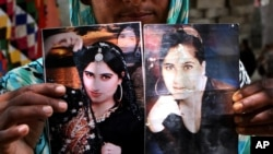 FILE - A family member shows pictures of slain model Qandeel Baloch, in Shah Sadderuddin, Pakistan, July 22, 2016.