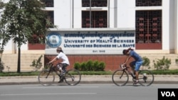Two cyclists are seen riding past the University of Health Sciences, on 8 August 2015. (Photo: Ouch Nida/VOA Khmer)