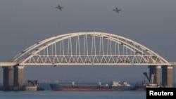 俄罗斯截停乌克兰船只后,俄罗斯喷气式战斗机飞过一座连接俄罗斯大陆与克里米亚半岛的桥梁,桥下面有一艘货船。