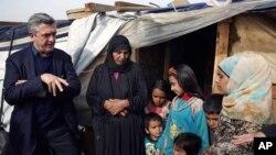 Filippo Grandi, à gauche, le Haut-commissaire de l'ONU pour les réfugiés, parle avec une famille syrienne au camp de Saadnayel, Liban, 22 janvier 2016.