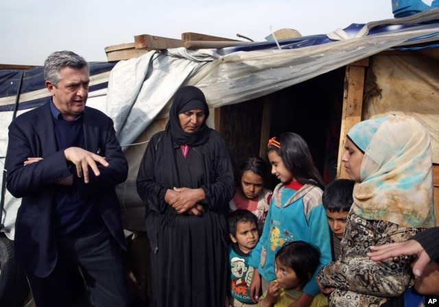 FILE - Filippo Grandi, left, the U.N. High Commissioner for Refugees, speaks with a Syrian family at a camp in Saadnayel, in the Bekaa valley, Lebanon, Jan. 22, 2016. Grandi said nearly two-thirds of refugees are women and children.