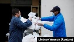 Ilustrasi. Hazim Macky mengambil makan berbuka puasa dari Mohamed Saleem yang disiapkan untuk masyarakat di luar Asosiasi Muslim Puget Sound pada hari pertama Ramadan di tengah wabah corona di Redmond, Washington, AS, 24 April 2020. (Foto: Reuters/Lindsey