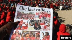 A Zimbabwean opposition party Movement For Democratic Change (MDC) supporter holds a party newsletter at an election rally, about 90 km (56 miles) east of the capital Harare, July 23, 2013.