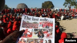 file: A Zimbabwean opposition party Movement For Democratic Change (MDC) supporter holds a party newsletter at an election rally, about 90 km (56 miles) east of the capital Harare, July 23, 2013.
