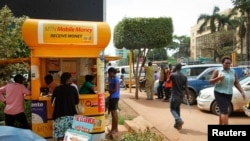 In this photo taken Sept. 29, 2016, Ugandans use a mobile money point in Kampala. Mobile money has become a way of life for many Africans.