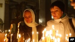 People light candles inside an Orthodox church in St.Petersburg during a day of national mourning for the plane crash victims, Russia, Nov. 1, 2015.