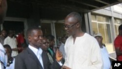 Press Union of Liberia president Peter Quaqua (left) with journalist Aaron Kollie