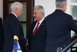 FILE - Vice President Mike Pence shakes hands with Turkish Prime Minister Binali Yildirim after a meeting at the White House, Nov. 9, 2017, in Washington.