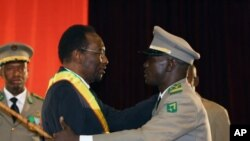 Mali's Interim President Dioncounda Traore, left, is congratulated by coup leader Amadou Haya Sanogo after being sworn in at a ceremony in Bamako, Mali Thursday, April 12, 2012. Traore, Mali's parliamentary head, took office as interim president Thursday,