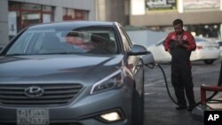A attendant fills up a car at a gas station in Jiddah, Saudi Arabia, Sept. 15, 2015. Oil prices rose above $50 a barrel Thursday for the first time this year.