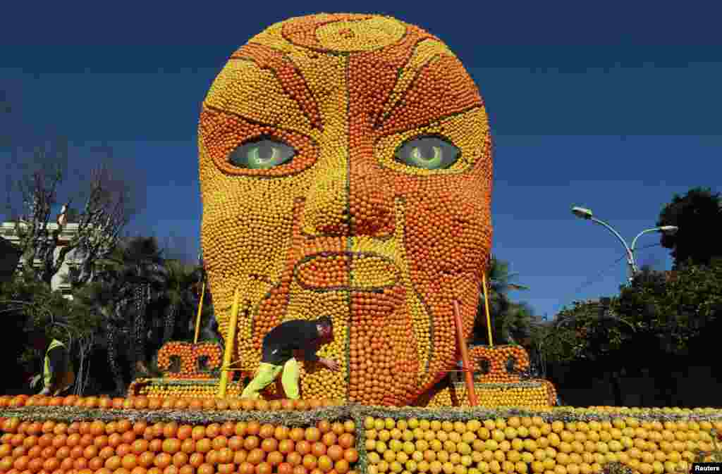 "A worker puts the final touches to a replica of a Beijing opera mask made with lemons and oranges during the 82th Lemon festival in Menton, France. It took over 20,000 hours work for teams to set up the festival and some 145 metric tons of lemons and oranges are used to make displays during the 82th festival, which is themed ""Tribulations of a lemon in China""."