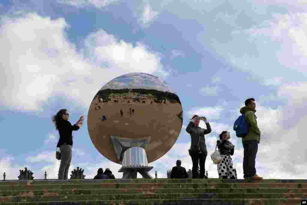 """Visitors take a picture of the front of the """"Sky Mirror"""" by British-Indian artist Anish Kapoor in the Versailles castle in Versailles, France."""