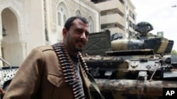 A rebel fighter beside a captured government tank in Misrata, Libya, April 22, 2011