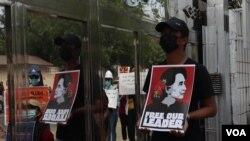 បុរសម្នាក់កាន់បដាដែលមានរូបអ្នកស្រី Aung San Suu Kyi នៅពេលចូលរួមបាតុកម្មទាមទារឲ្យមានការដោះលែងអ្នកស្រីនិងមេដឹកនាំស៊ីវិលដទៃទៀត ក្នុងទីក្រុងរ៉ង់ហ្គូន ប្រទេសមីយ៉ាន់ម៉ា កាលពីថ្ងៃទី១៥ ខែកុម្ភៈ ឆ្នាំ២០២១។
