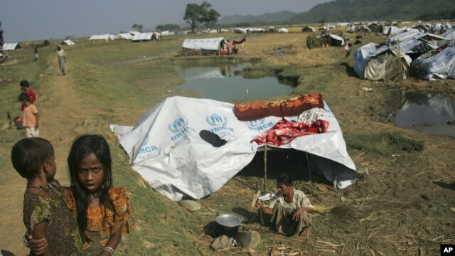 Muslim refugees stand near their tent at Sin Thet Maw relief camp in Pauk Taw township, Rakhine state, western Myanmar, November 10, 2012.