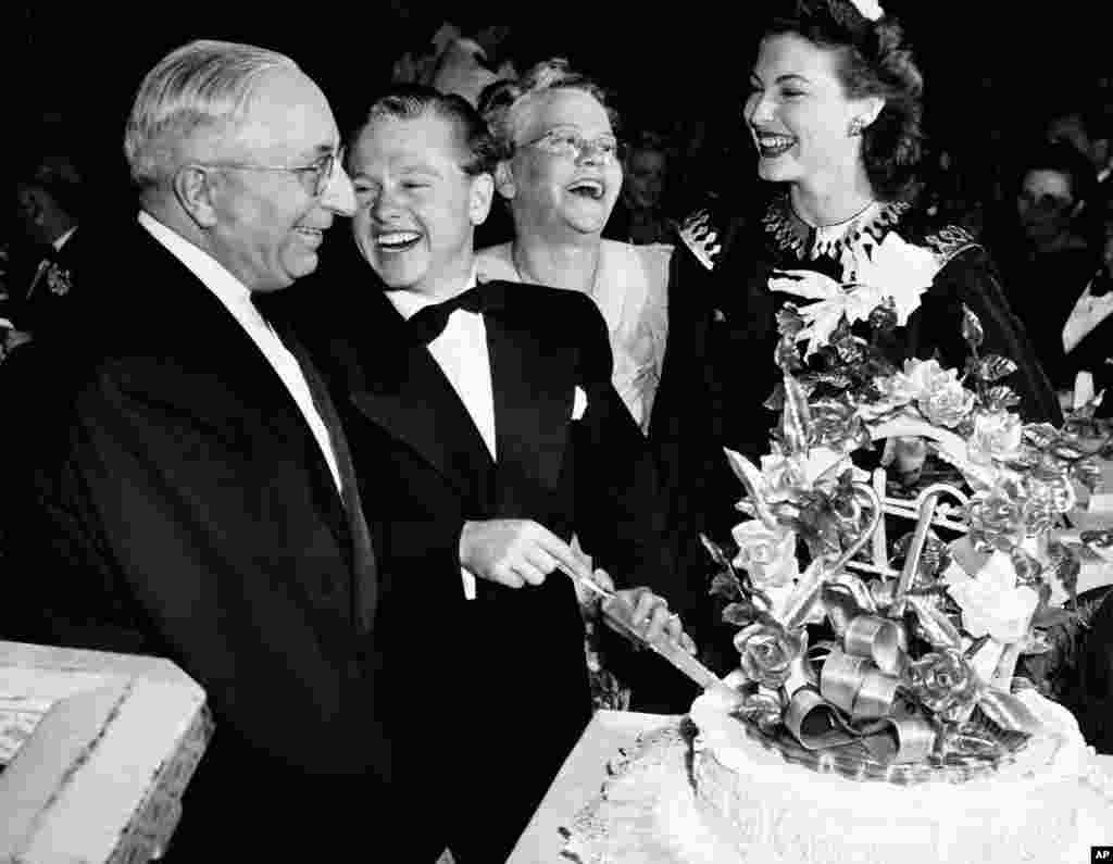 Film actor Mickey Rooney celebrates his 21st birthday at a party in a Hollywood night club. Here he slices his birthday cake with (left to right) Louis B. Mayer, studio head; Mrs. Nell Pankey, his mother, and Miss Ava Gardner, Hollywood, California, Sept. 23, 1941.